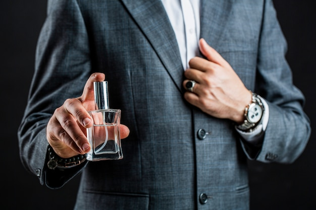 Homem segurando frasco de perfume. entregue com relógio de pulso em um terno de negócio.