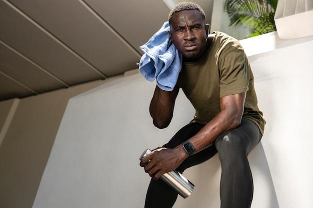 Homem segurando frasco e toalha