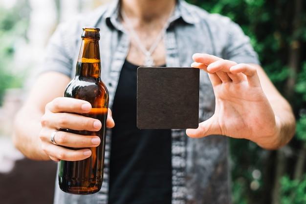 Homem, segurando, garrafa cerveja marrom, e, pretas, em branco, cartão, em, mãos
