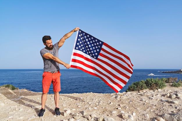 Homem segurando grande acenando a bandeira dos eua ao ar livre. dia da independência dos estados unidos da américa. conceito de povo patriótico americano
