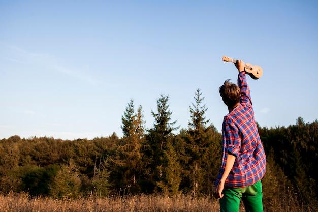 Homem segurando guitarra ukulele no ar