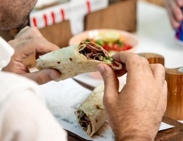Homem segurando hambúrguer de carne embrulhado em pão sírio