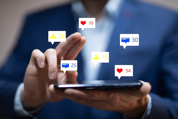 Homem segurando ícones de mídia social com telefone inteligente