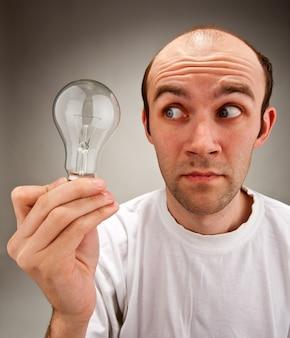 Homem segurando lâmpada elétrica