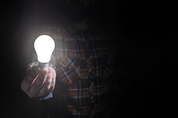 Homem segurando lâmpada incandescente