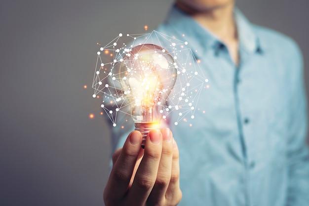 Homem segurando lâmpadas, ideias de novas ideias com tecnologia inovadora e criatividade.
