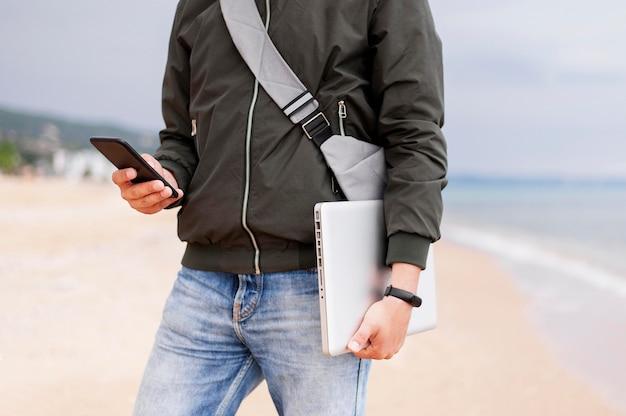 Homem segurando laptop e smartphone na praia
