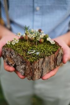 Homem, segurando, levantar, para, alianças, feito, de, latido árvore, e, musgo, anel acoplamento
