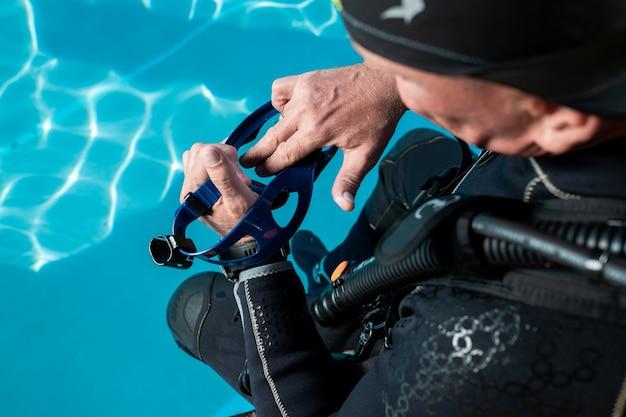 Homem segurando máscara de mergulho na piscina