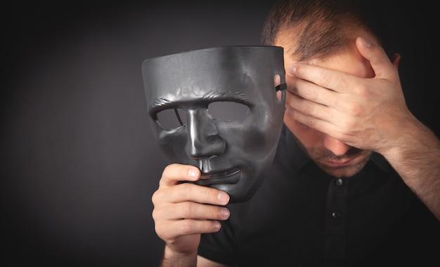 Homem segurando máscara preta. falsa, anônima