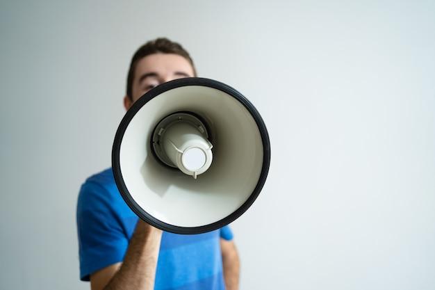 Homem, segurando, megafone, frente, seu, rosto
