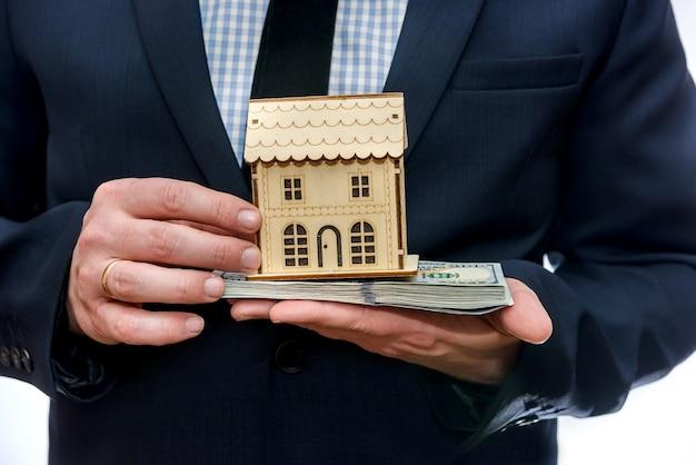 Homem segurando modelo de casa de madeira e notas de dólar