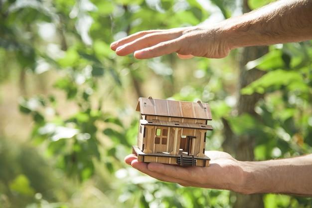 Homem segurando modelo de casa de madeira na natureza.