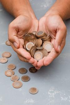 Homem segurando moedas na palma da mão.