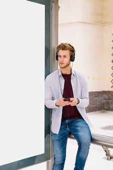 Homem, segurando móvel, e, escutar música