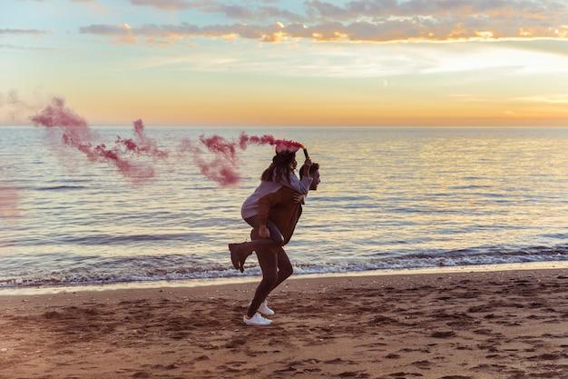 Homem, segurando, mulher, com, cor-de-rosa, bomba fumaça, ligado, costas