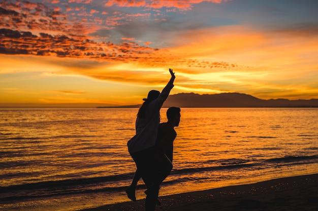 Homem, segurando, mulher, costas, ligado, noite, costa mar
