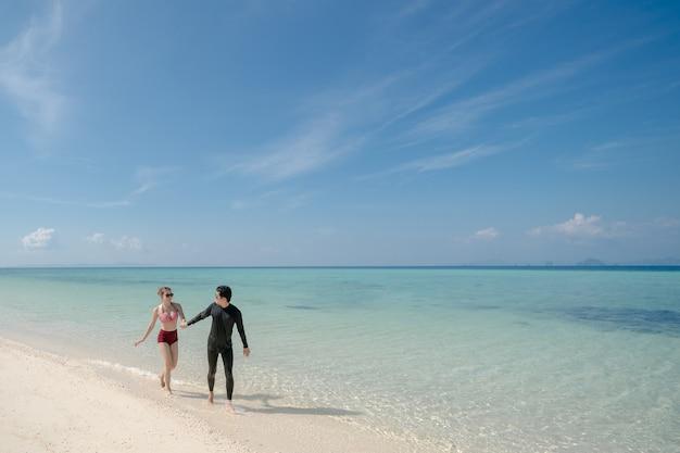 Homem segurando mulher de biquíni de mão andar na água do mar, na praia de areia branca. paisagem azul do mar e do céu. férias de verão.