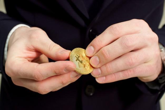 Homem segurando na mão o símbolo da moeda criptográfica bitcoin - dinheiro virtual eletrônico para web banking.