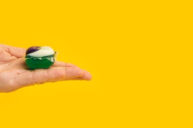 Homem segurando na palma da mão uma cápsula de detergente para máquina de lavar em um fundo amarelo