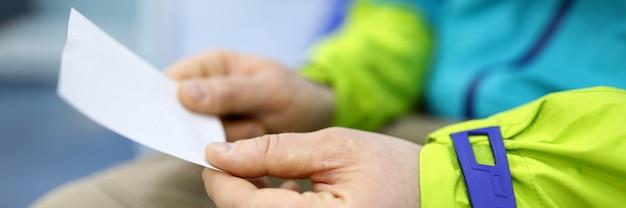 Homem segurando nas mãos de folha de papel com o número em close-up de linha