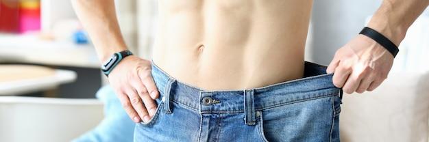 Homem segurando nas mãos jeans tamanho grande, mostrando seu progresso antes e depois que ele começou a treinar closeup