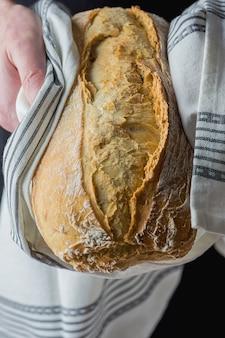 Homem segurando nas mãos recém-assados à mão crafted pão rústico embrulhado em pano branco.