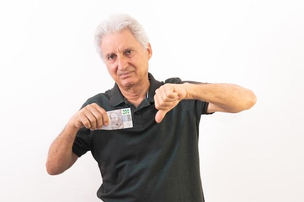 Homem segurando nota de 200 reais com gesto em uso da grande desvalorização da moeda