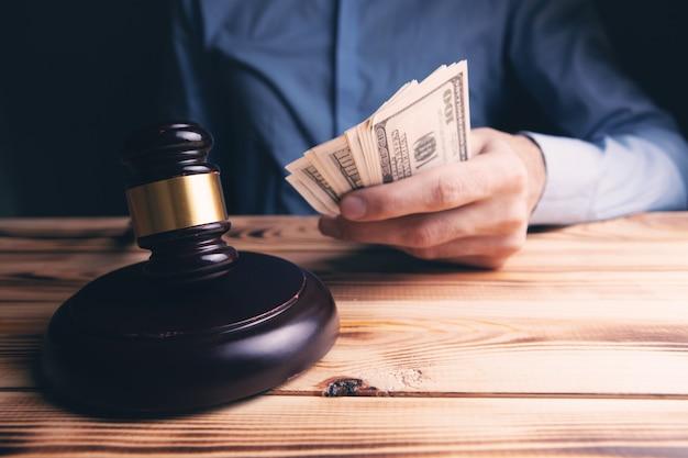 Homem segurando notas de dólar ao lado do martelo do juiz