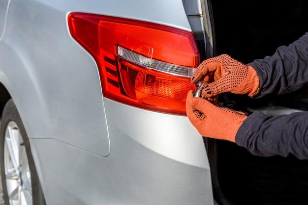Homem segurando novas lâmpadas perto de faróis de carros