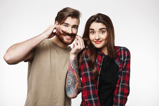 Homem segurando o cabelo de mulher como é bigode, sorrindo alegremente.