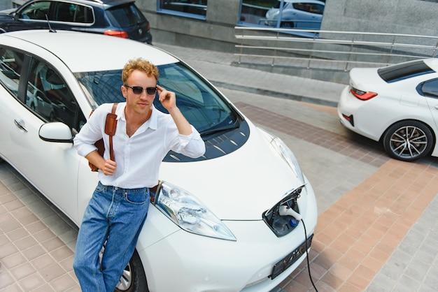 Homem segurando o cabo de carregamento de energia para carro elétrico no estacionamento ao ar livre. e ele vai conectar o carro à estação de recarga no estacionamento perto do shopping center