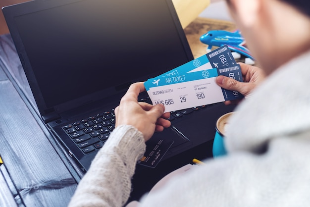 Homem segurando o cartão de crédito e compra passagens de avião na internet