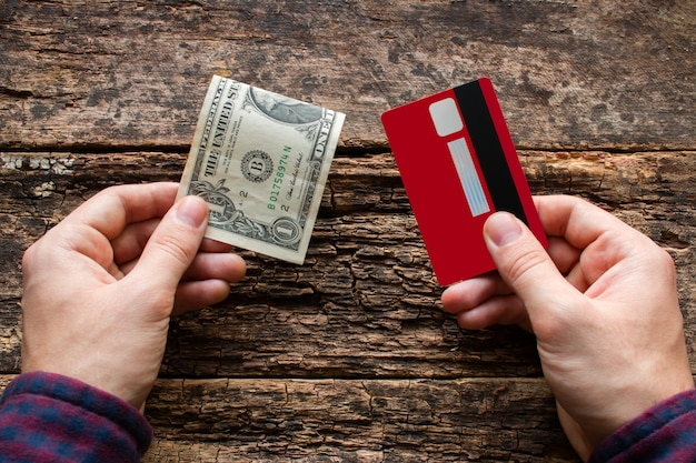 Homem segurando o cartão de crédito e dinheiro