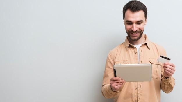 Homem segurando o cartão de crédito e tablet com espaço de cópia