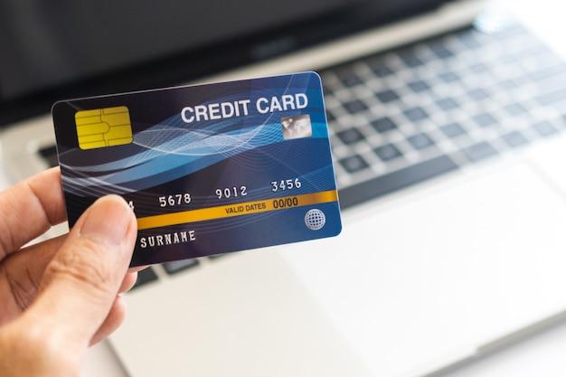 Homem segurando o cartão de crédito no laptop. compras on-line na internet usando um laptop