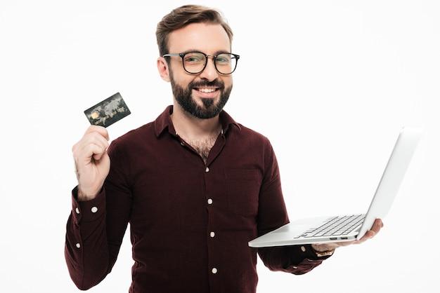 Homem segurando o cartão de débito e o computador portátil ... compras on-line