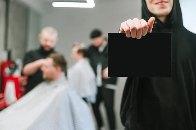 Homem segurando o cartão preto em branco, concentre-se no espaço em branco na barbearia