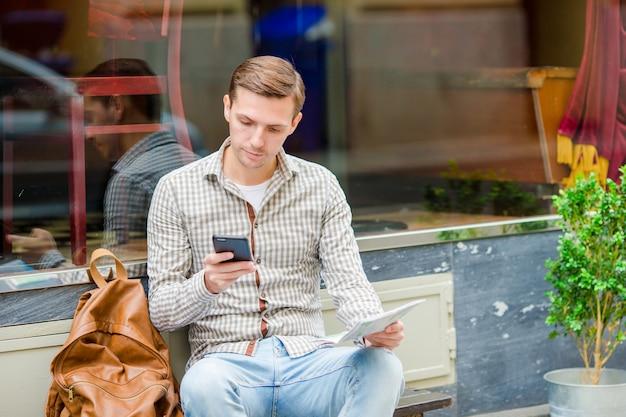 Homem segurando o celular ao ar livre na rua. homem usando smartphone móvel.
