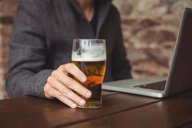 Homem segurando o copo de cerveja e usando o laptop