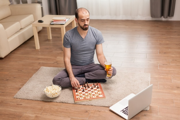Homem segurando o copo de cerveja enquanto joga xadrez online durante o auto-isolamento.