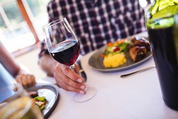 Homem segurando o copo de vinho no restaurante