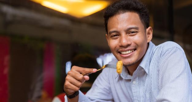 Homem segurando o frango frito para comer em uma refeição no brunch no restaurante com felicidade em vez de relaxar