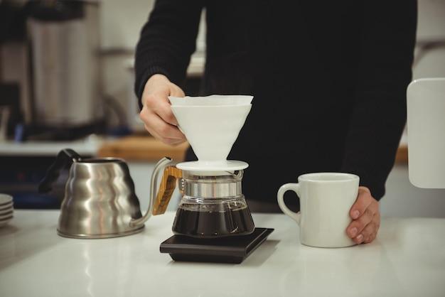 Homem segurando o funil do filtro e a caneca de café