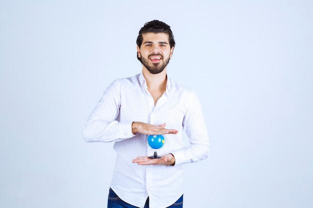 Homem segurando o globo terrestre entre as mãos