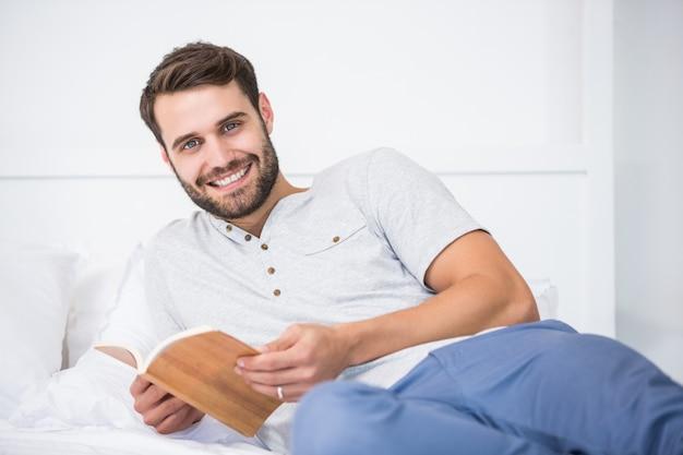 Homem segurando o livro na cama em casa