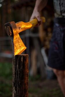 Homem segurando o machado afiado na madeira cortada no chão