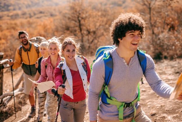 Homem segurando o mapa e liderando o pequeno grupo de caminhantes.