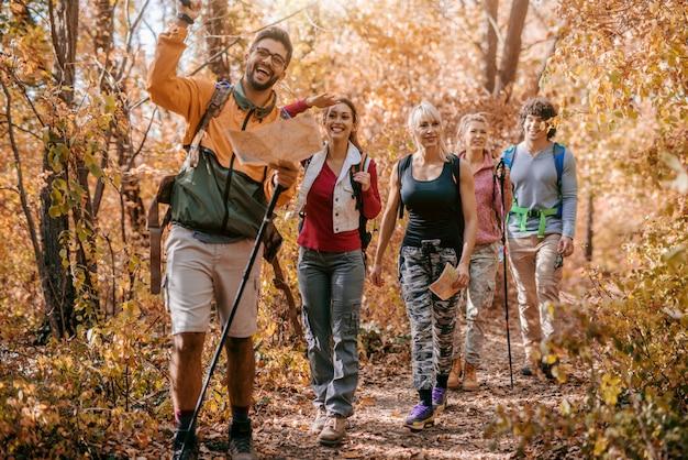 Homem segurando o mapa e mostrando outros caminhantes o caminho certo enquanto caminhava na floresta.