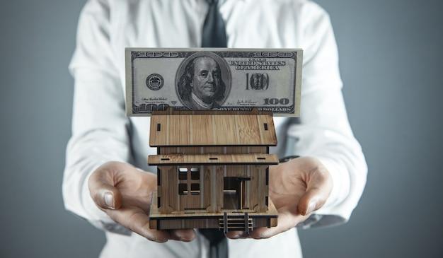 Homem segurando o modelo da casa com dinheiro.